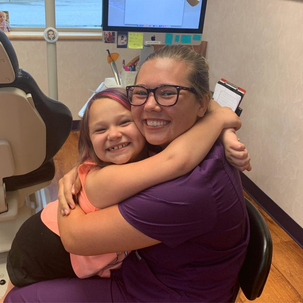 Roeder Orthodontics team member hugging a patient