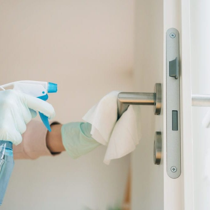 Woman cleaning a door handle with a disinfection spray